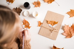 autumn craft for kids. animal Fox made from maple leaf. childrens art and creative. handicraft made from natural materials. girl draws with paints.