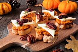 Autumn crostini appetizers with pumpkin spread, cheese and nuts. Side view serving scene on a rustic wood background.