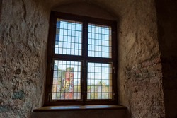 Autumn day light going through vintage stained-glass window in very thick wall niche in the dark medieval castle. Ruins of medieval castle behind the window.