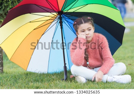 Autumn depression. Spring style. depressive mood in autumn rainy weather. Little girl tired under colorful umbrella. Multicolored umbrella for little happy girl. Rainbow after rain. feeling depressed.