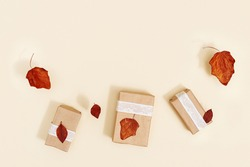 Autumn DIY gift boxes from craft paper decorated red dry leaves on beige background. Autumn season holiday layout, fall time concept,  zero waste holidays. Flat lay, top view.
