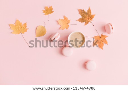 Autumn  elegant composition. Cup of coffee and dry leaves on pastel pink background. Flat lay, top view, copy space