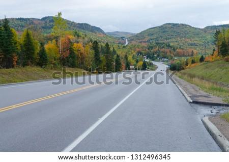 Autumn endless road under cloudscape, Quebec, Canada #1312496345