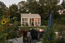 Autumn evening in a beautiful garden with a fire lit raised beds and a white Victorian style greenhouse with a cupola and weather vane in background