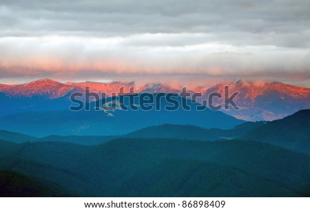 Autumn evening landscape with lust golden-pink sunlight on mountains and evening glow in sky