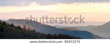 Autumn evening plateau landscape with lust golden-pink sunlight on mountains and evening glow in sky. Two shots stitch image.