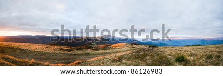 Autumn evening plateau landscape with lust golden-pink sunlight on mountains and evening glow in sky.