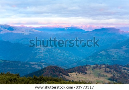 Autumn evening plateau landscape with lust golden-pink sunlight on mountains and evening glow in sky