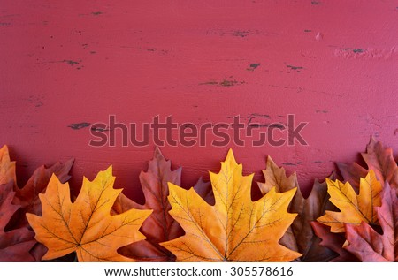 Autumn Fall background for Thanksgiving or Halloween with leaves and decorations on rustic wood table with copy space for your text here.