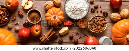 Autumn fall baking background with pumpkins, apples, nuts, food ingredients and seasonal spices, banner. Cooking pumpkin or apple pie and cookies for Thanksgiving and autumn holidays.