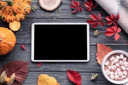 Autumn fall holiday background with pumpkin orange leaves cocoa cup tablet computer blank empty screen mock up on brown wooden table, happy halloween thanksgiving shopping sale, above top view