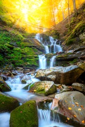 Autumn fall mountain waterfall stream in the rocks with colorful fallen dry leaves, landscape, natural seasonal background