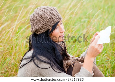 Autumn fall park grass sitting girl with paper tissue