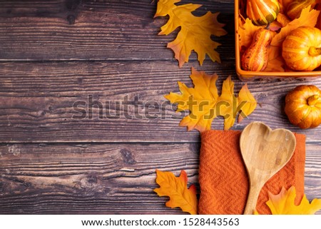 Autumn / Fall themed background with free space for words or to copy to. Orange color theme with leaves, pumpkins, squash, and cooking utensils on a wooden background.