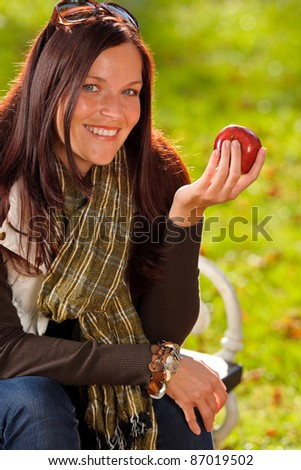 Autumn fashion smiling beautiful woman eat apple sunset nature park - stock photo