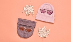 Autumn fashionable Flat lay. Woman Accessories Set. Trendy Beanie Hat, Glamour Stylish Sunglasses. Minimal Creative. Fall Hipster Girl fashion Outfit, autumnal Maple Leaf on orange