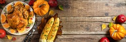 Autumn festive Thanksgiving background. Baked chicken or turkey, festive food for Thanksgiving dinner on wooden table. Table settings for Thanksgiving. Long format with copy space