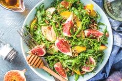 Autumn fig and arugula salad recipe. Whole vegan paleo fruit and vegetable fall salad idea. Homemade salad bowl with figs, arugula, peach and apple slices, nuts and honey.