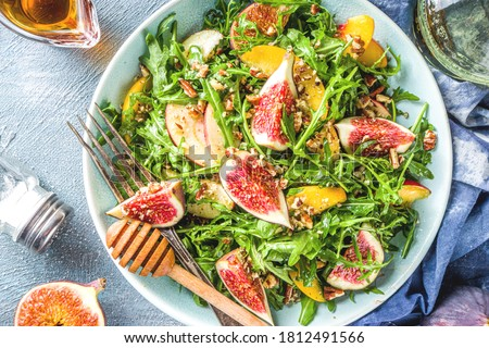Autumn fig and arugula salad recipe. Whole vegan paleo fruit and vegetable fall salad idea. Homemade salad bowl with figs, arugula, peach and apple slices, nuts and honey.  ストックフォト ©