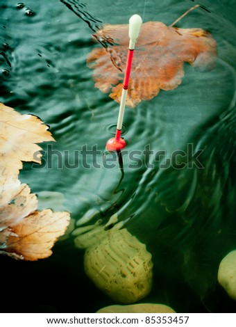 Autumn fishing. Bobber float in water with yellow leafs. - stock photo