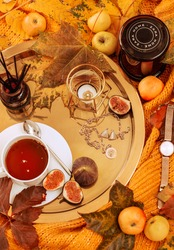 autumn flat desktop with a homely atmosphere, colorful autumn, yellow maple leaves,apples, figs and a Cup of tea