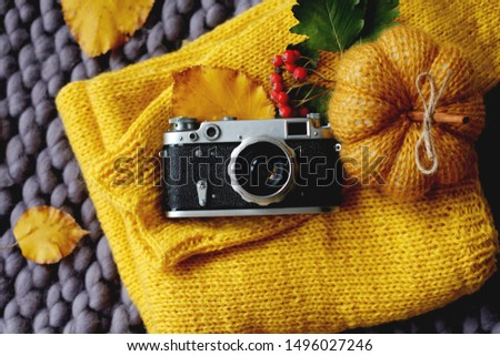Autumn flat lay background. Top view of vintage photo camera, yellow sweater, knitted blanket and pumpkin, fall leaves. Happy thanksgiving autumn background