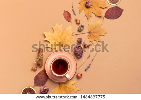 Autumn Flat lay composition. Cup of tea, autumn dry bright leaves, roses flowers, orange circle, cones, decorative pomegranate, cinnamon sticks on brown beige background top view. Autumn, fall concept