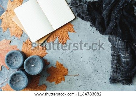 Autumn flat lay composition on a grey concrete background. Maple leaves, the open notebook with empty sheets, black aromatic candles and warm scarf. Mockup, top view. #1164783082