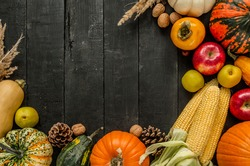 Autumn flat lay composition, with copy space on wooden background. Variety of edible and decorative gourds and pumpkins, walnuts, cones, apples, kaki fruit and corn on the cob.
