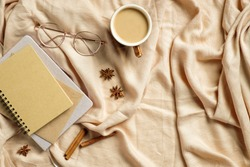 Autumn flatlay composition. Paper notebook, glasses, coffee cup on beige plaid. Autumn hygge style desk table or winter holiday concept.