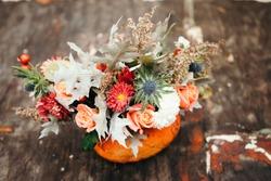 Autumn floral bouquet in a pumpkin vase for Halloween.