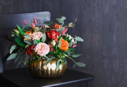 Autumn floral bouquet in colored punpkin vase on black chair, copy space