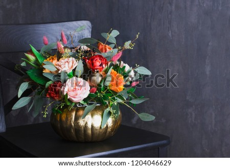 Autumn floral bouquet in colored punpkin vase on black chair, copy space #1204046629