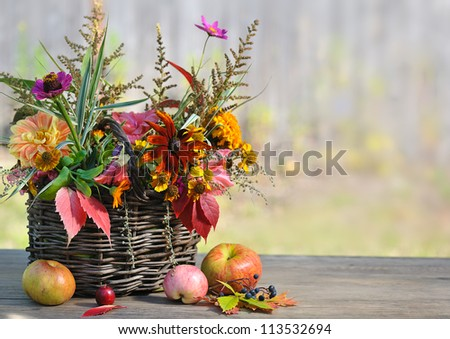 autumn floral composition in basket with apples