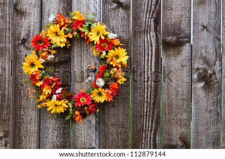 Autumn flower wreath on rustic wooden fence