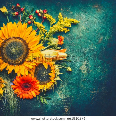 Autumn flowers arrangements made of  sunflowers, leaves and canina berries on rustic vintage background , top view, place for text, retro toned