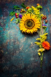 Autumn flowers bunch with sunflowers on dark vintage background, top view, frame