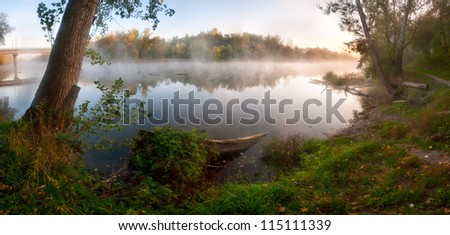 Autumn fog over the river, the sun shines the wood on shore, outdoors
