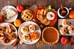 Autumn food concept. Selection of pies, appetizers and desserts. Above view table scene over a rustic wood background.