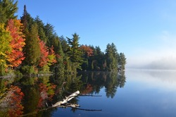 Autumn forest reflected in water. Colorful autumn morning in Ontario.