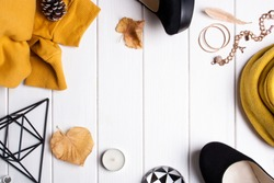 Autumn frame with female accessories. Shoes, yellow sweater and autumn leaves on a white wooden background top view
