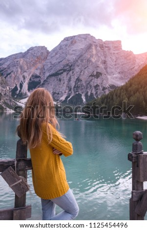 autumn - girl and view of well-known tyrolean lake lago di Braies Dolomites Italy #1125454496