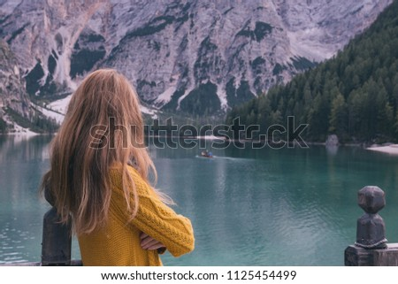 autumn - girl and view of well-known tyrolean lake lago di Braies Dolomites Italy #1125454499