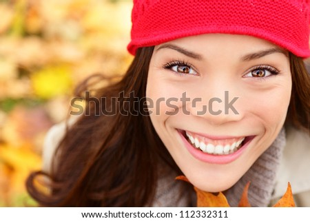 Autumn girl in fall colors smiling happy in closeup portrait. Fall woman cheerful and beautiful. Multiethnic Asian Caucasian young woman.
