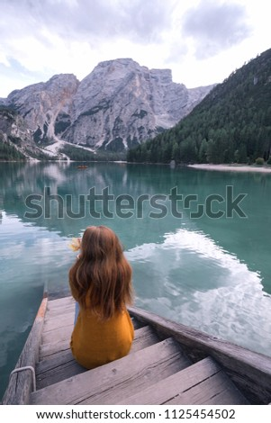 autumn - girl sits on the pier and view of well-known tyrolean lake lago di Braies Dolomites Italy #1125454502