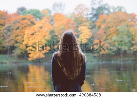 Autumn girl standing backwards and watching nature. Autumn forest colors with girl back view. Outdoor autumn landscape. Orange autumn portrait. Orange tranquility - woman watching woods outdoor #490884568
