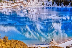 Autumn gives way to winter, air temperature drops and the water in the lake begins to freeze. Texture and patterns of ice on the serene water surface of mountain lake; Big Almaty lake in Kazakhstan