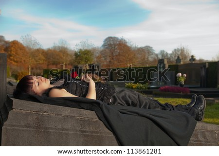 Autumn graveyard and a young gothic girl dead on a tombstone