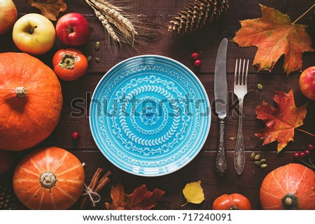 Autumn Halloween or thanksgiving day table setting. Fallen leaves, pumpkins, spices, empty plate and vintage cutlery on wooden table. Thanksgiving background mock up. Top view, toned image