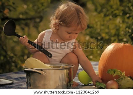 autumn harvest. Closeup of one small cook boy at picnic sitting with black ladle pot orange pumpkin and other vegetables playing with food sitting on blue checkered plaid on natural background